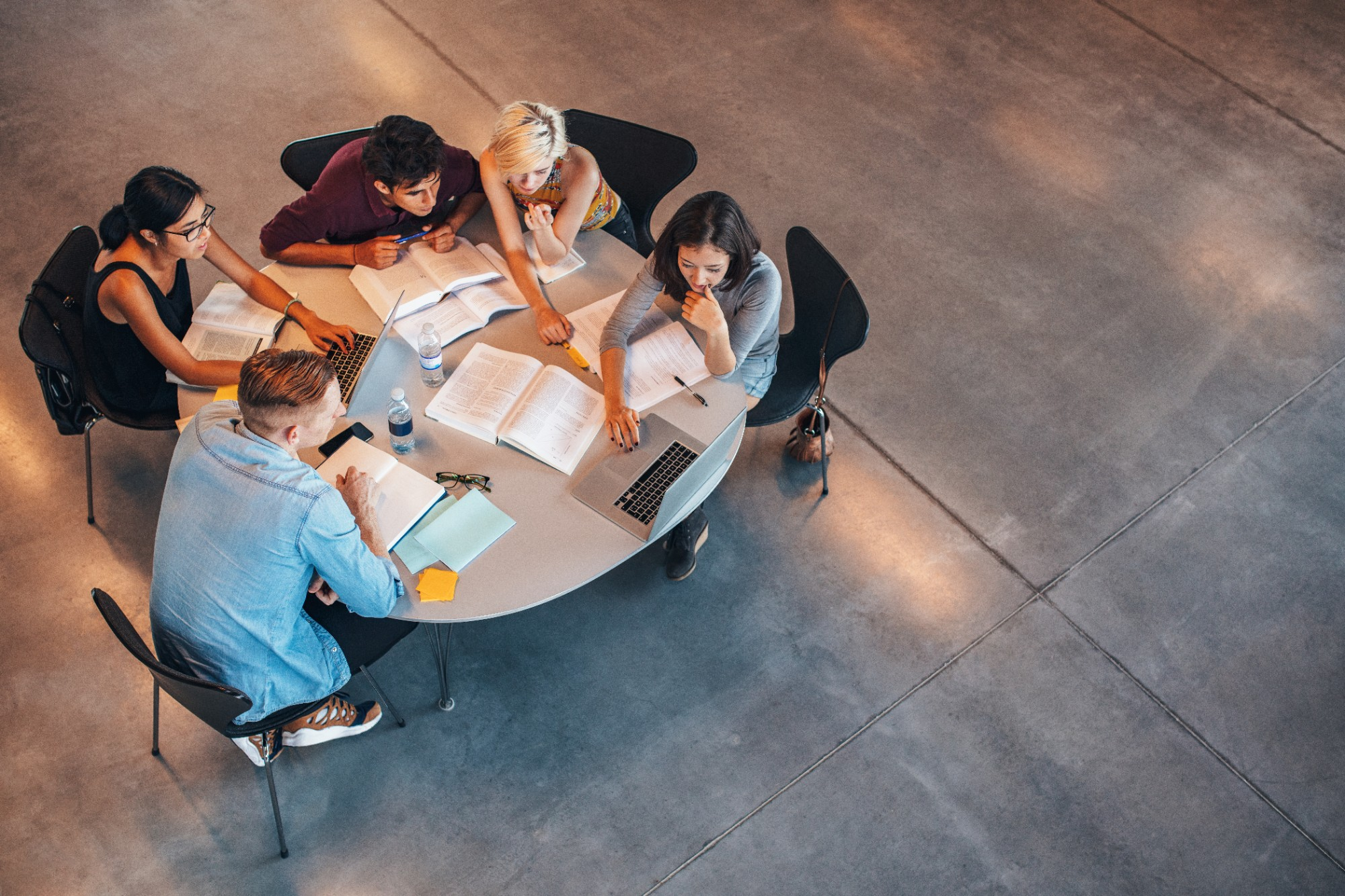 Multiracial group of young students studying together