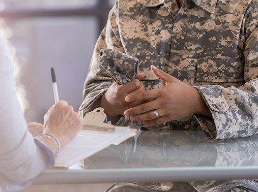 A mental health professional takes notes while talking with a soldier