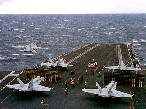 An F-14 Tomcat launches as four F/A-18 Hornets wait to launch from the aircraft carrier USS Enterprise in the Adriatic Sea, February 23, 1999