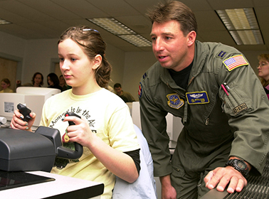 Fifth-grader Catherine Newcome, at the yoke, gets a feel for flying a small plane on a computer simulator during a National Guard Starbase exercise in Martinsburg, W.Va.