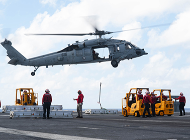 An MH-60S Knight Hawk helicopter drops off supplies from the dry cargo and ammunition ship USNS Charles Drew
