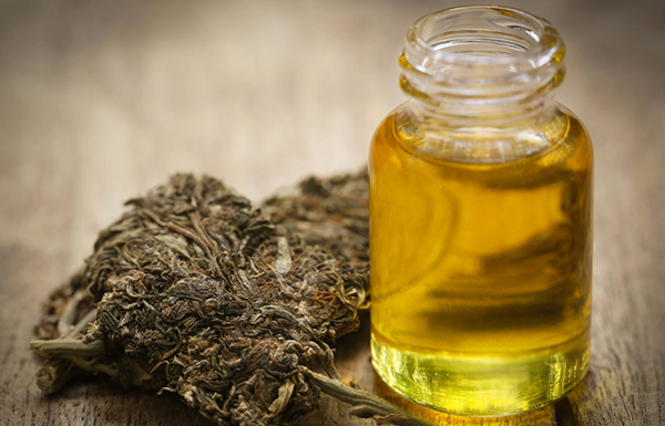 cannabis next to a bottle of cannabis oil on a wooden table, photo by bdspn/Getty Images