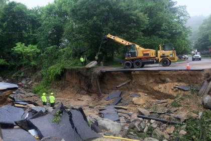 A crew works to repair a road destroyed by flooding on May 31, 2018 in Ellicott City, Maryland. On May 27 Ellicott City experienced a devastating flood for the second time in two years.