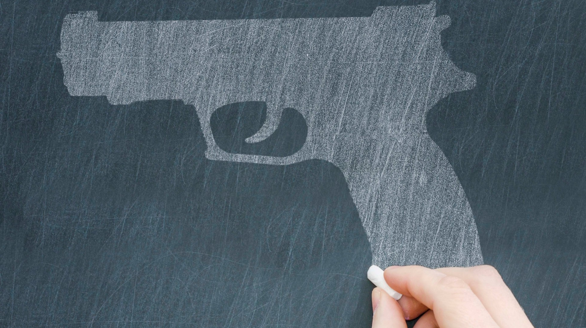 A hand holding a piece of chalk up to a drawing of a handgun on a chalkboard