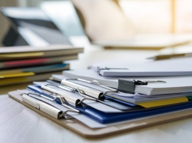 Stack of clipboards and documents on a desk, photo by juststock / Getty Images