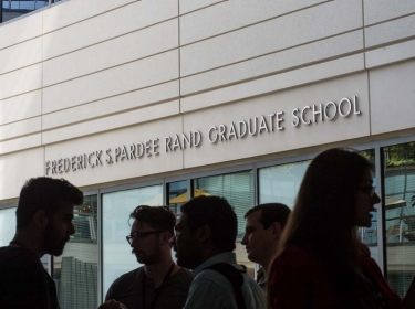 Silhouettes of students talking in front of Frederick S. Pardee RAND Graduate School, photo by RAND Corporation