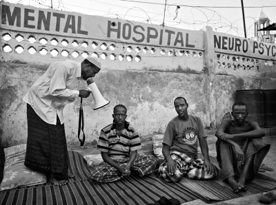 An Imam recites verses from the Koran through a megaphone in an effort to 'heal' patients with mental health problems in Mogadishu, Somalia