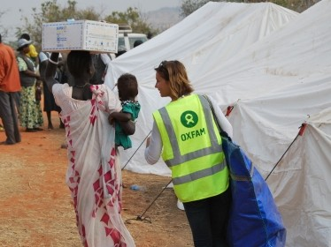 An Oxfam member of staff helps to carry one family's newly received non-food items home in UN House, Juba