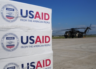 Pallets of food, water and supplies staged to be delivered in Haiti, helicopter, flight line, USAID, earthquake