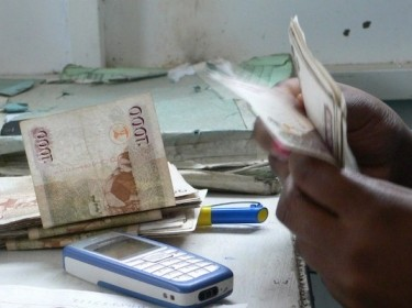Kenyan with cash, conducting a mobile banking transaction, photo by Scott Mainwaring/CC BY-SA 2.0