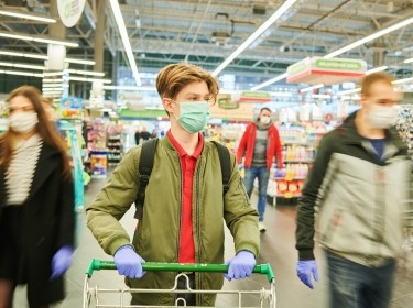 People shop while wearing mask and protective gloves, photo by Kadmy/Adobe Stock