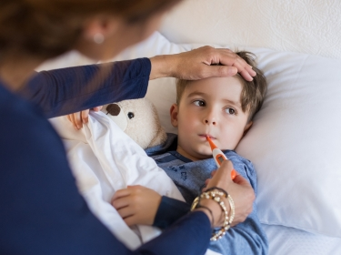 Checking a young boy's temperature, photo by Rido/Adobe Stock