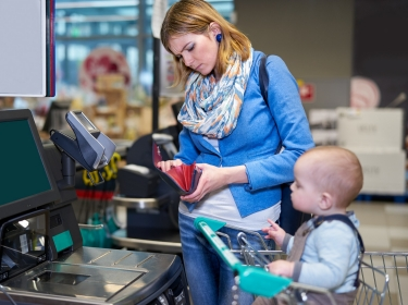 Young woman with baby paying at grocery, photo by Yummy pic/Adobe Stock