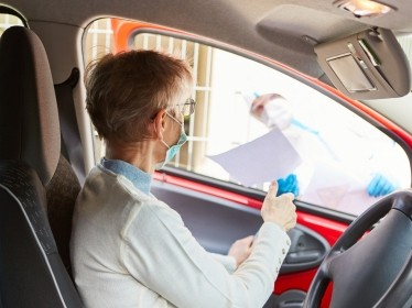 Woman begins drive-through coronavirus testing, photo by Robert Kneschke/Adobe Stock