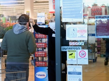 An employee checks the temperature of a man at the entrance of a supermarket, as the spread of COVID-19 continues, Milan, Italy March 23, 2020, photo by Daniele Mascolo/Reuters