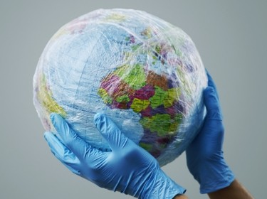 Gloved hands holding a globe wrapped in plastic, photo by nito/Adobe Stock