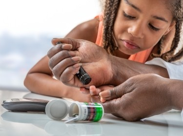 Diabetic child with glucometer learning to check blood sugar level at home, photo by JPC-PROD/Adobe Stock