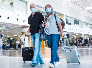 Seniors wearing face masks, walking in the airport, photo by Fabio/Adobe Stock
