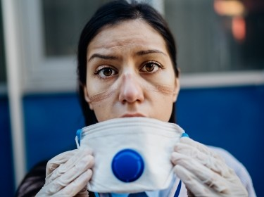 Exhausted medical worker taking off coronavirus protective gear N95 mask, photo by eldar nurkovic/Adobe Stock