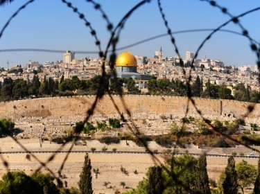 View from the Mount of Olives to the Dome of the Rock, through barbed wire, photo by gkuna/Adobe Stock