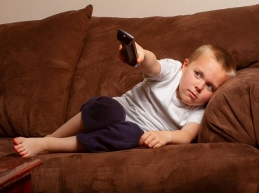 Lazy boy on couch watching TV, photo by Tracy King/Adobe Stock