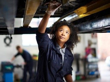 Female mechanic standing under a car in a garage