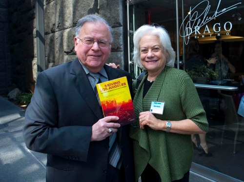 Marty Wachs, with his wife Helen, holds up a copy of the RAND report Moving Los Angeles: Short-Term Policy Options for Improving Transportation, which he co-authored. The couple is  pictured at a 2012 RAND event. Photo by Diane Baldwin/RAND Corporation