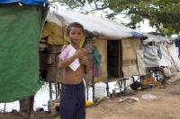 Boy in slum holding book want to go school