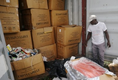 An agent stands next to a container full of illegal and false drugs seized by Ivorian authorities in Abidjan, Ivory Coast, November 6, 2018, photo by Luc Gnago/Reuters