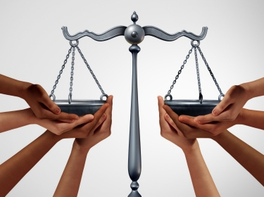 Diverse people holding the scales of justice , photo by freshidea/Adobe Stock
