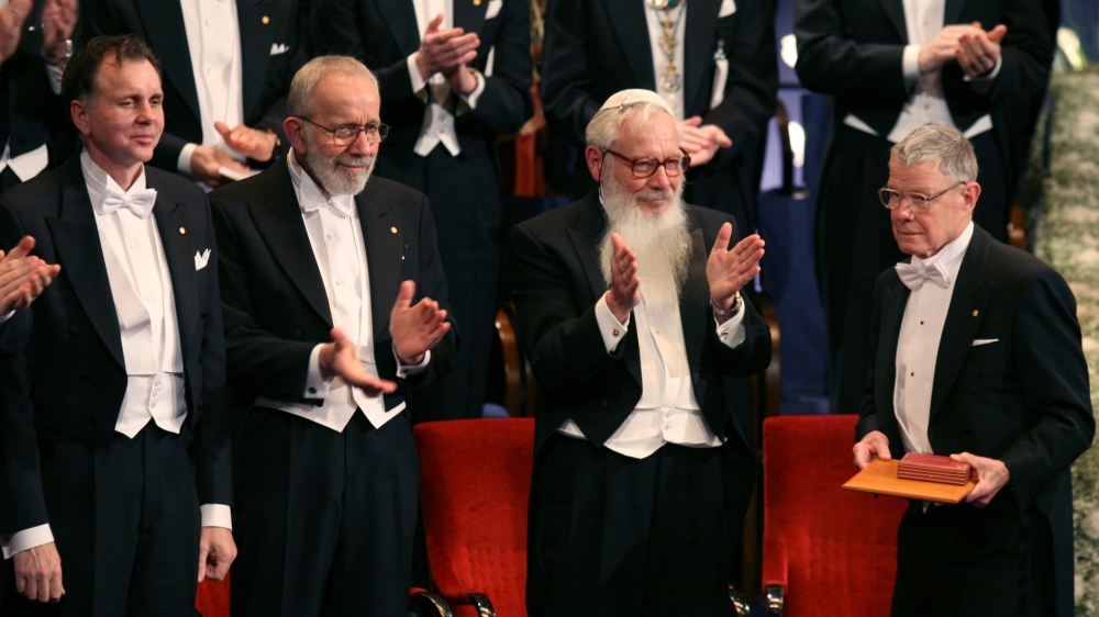 Thomas C. Schelling (right) is applauded by fellow Nobel laureates at the Stockholm Concert Hall, Sweden, December 10, 2005