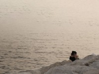 Two people embrace while sitting on a rocky shoreline and looking across the horizon, Antelias, Lebanon, May 2009
