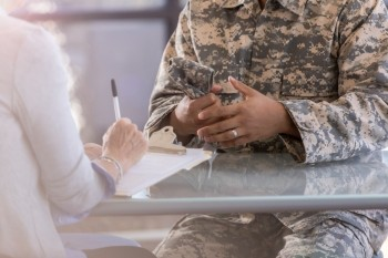 A mental health professional takes notes while talking with a soldier, photo by asiseeit/Getty Images