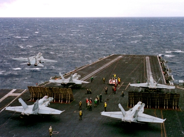 An F-14 Tomcat (left) launches as four F/A-18 Hornets wait to launch from the aircraft carrier USS Enterprise in the Adriatic Sea, February 23, 1999, photo by PO1 Benjamin D. Olvey/U.S. Navy