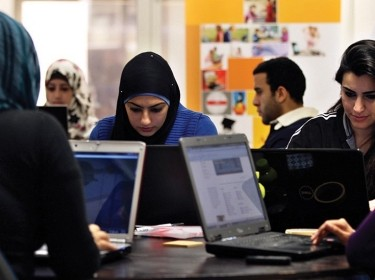 Young entrepreneurs work on their laptops at the Amman-based Oasis 500