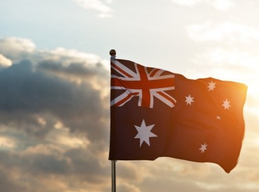 Waving Australia flag in the air at sunset, photo by baona/Getty Images