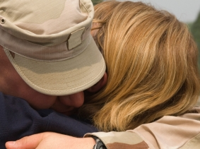 A soldier hugging his wife or girlfriend upon his return from deployment, photo by JPecha/iStock