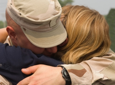 A soldier hugging his wife or girlfriend upon his return from deployment