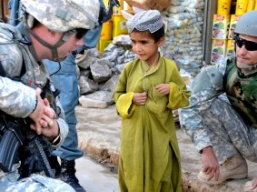 An Afghan National Interpreter and U.S. Army soldier talk with an Afghan boy during a patrol at a bazaar in the Zabul province of Afghanistan June 29, 2010, photo by  SSgt. William Tremblay/U.S. Army