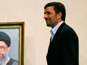 Iran's President Mahmoud Ahmadinejad walks past a portrait of Iran's Supreme Leader Ayatollah Ali Khamenei as he arrives at a news conference in Istanbul, May 9, 2011