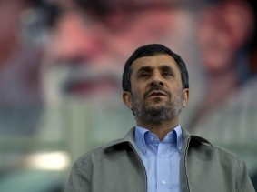 Iran's President Mahmoud Ahmadinejad stands for the national anthem beneath a portrait of Supreme Leader Ayatollah Ali Khamenei during a gathering of reformed drug addicts in Tehran, June 26, 2011