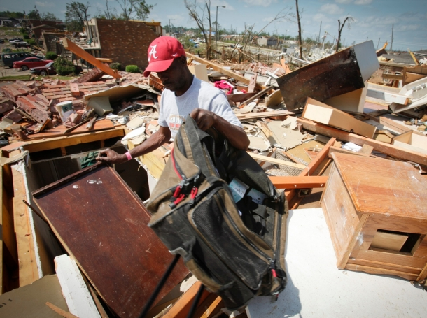 Sydney Maxwell looks for his belongings in his apartment destroyed in April 27's deadly tornados in Tuscaloosa, Alabama, May 2, 2011, photo by Lee Celano/Reuters