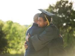 A father hugging his son on graduation day, photo by digitalskillet/Getty Images
