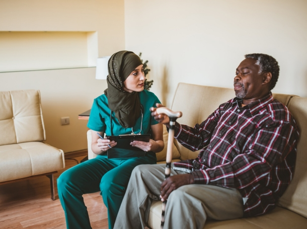 Doctor talking with a senior patient with a walking stick, photo by RealPeopleGroup/Getty Images