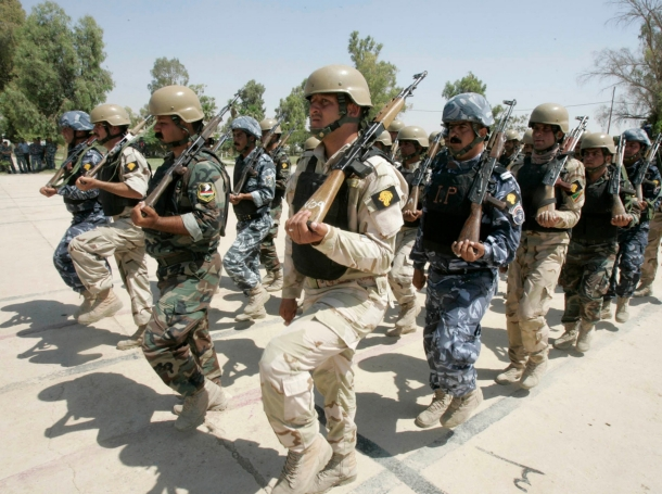 Iraqi soldiers, policemen, and Kurdish Peshmerga troops, a mixed squad put together to secure disputed areas in the north of the Iraqi capital, stand at attention during a parade, June 20, 2011, photo by Ako Rasheed/Reuters