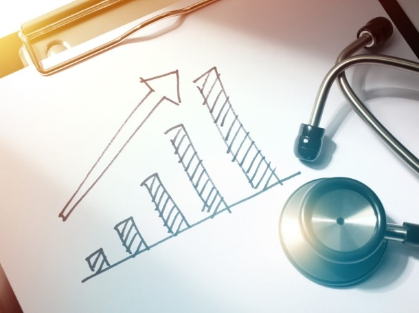 A stethoscope on an increasing bar chart, photo by blackred/Getty Images