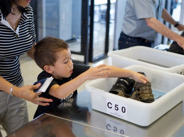 A child puts his shoes in a bin while going through a TSA security checkpoint in the Newark Liberty International Airport in Newark, New Jersey, July 28, 2011, photo by Lucas Jackson/Reuters