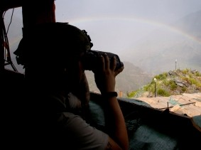 A U.S. soldier uses a pair of binoculars to scan an area with a rainbow after a firefight with the Taliban at Outpost Bari Alai in Ghaziabad district in Kunar, Afghanistan, September 15, 2011, photo by Erik de Castro/Reuters