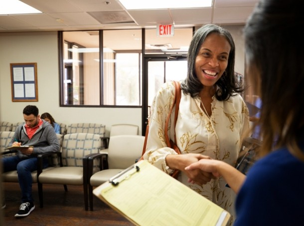 A patient shakes hands with a nurse in a medical office lobby, photo by SDI Productions/Getty Images