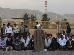 :An Iranian cleric talks to students who are forming a human chain around the Uranium Conversion Facility to show their support for Iran's nuclear programme in Isfahan, Iran, November 15, 2011, photo by Morteza Nikoubazl/Reuters